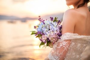 bride holding bouquet near the ocean