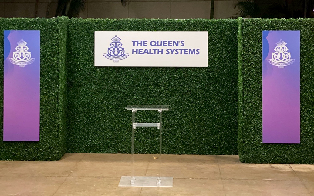 Faux Boxwood panels with Queen's Health Systems Signs