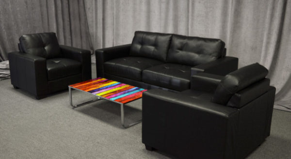 Black leather loveseat in lounge setting