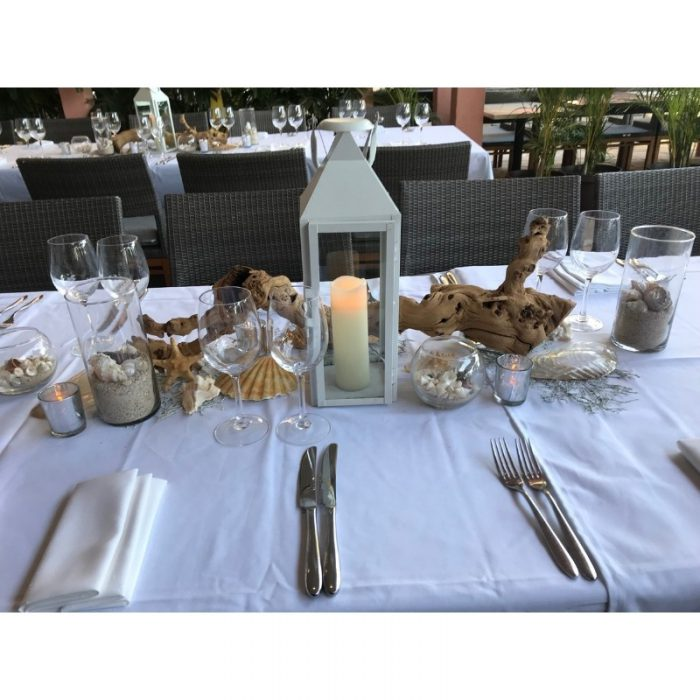 White lantern with candle on table