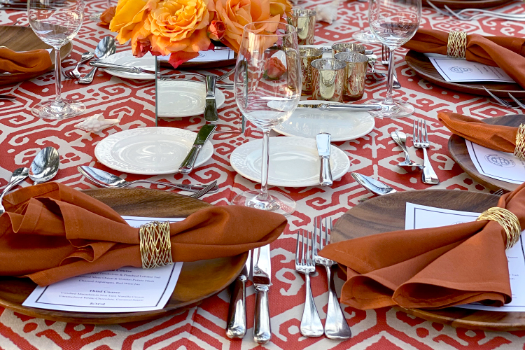 Table setting with burnt orange table linens and wood chargers